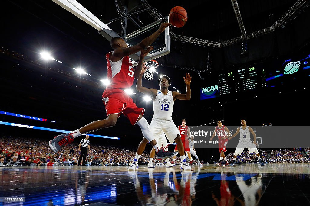Delon Wright of the Utah Utes saves the ball from going out of bounds as Justise Winslow of the Duke Blue Devils defends during a South Regional...