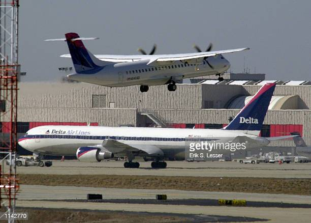 Delta Air Lines 767 is moved along the tarmac as another aircraft takes off February 8 2002 at Hartsfield Atlanta International Airport Authorities...