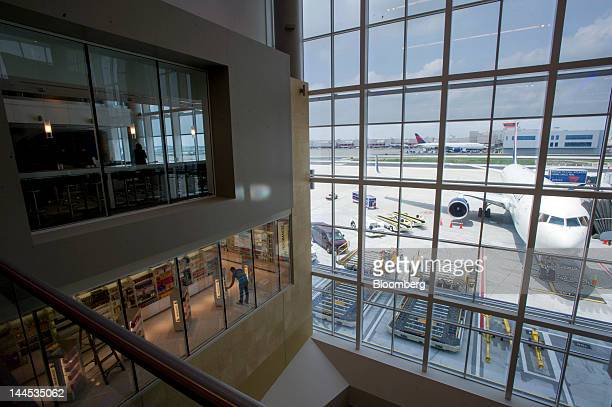 A Delta Air Lines Inc jet sits on the concourse as a worker puts new items on the shelf at the Maynard H Jackson Jr International Terminal at...
