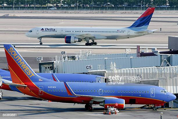 Delta Air Lines jet taxis beyond parked Southwest Airlines planes at McCarran International Airport September 12 2005 in Las Vegas Nevada Delta's...