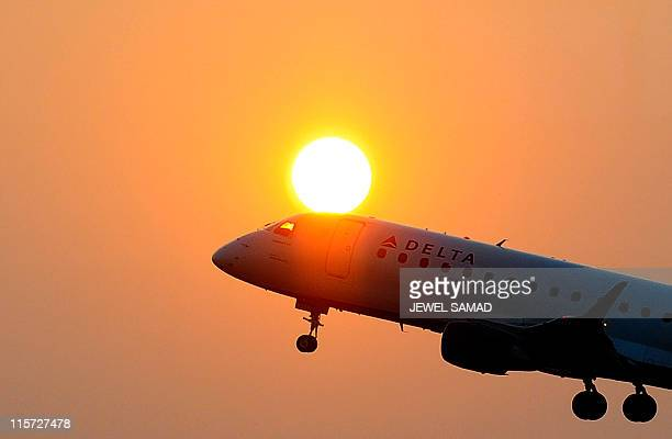 A Delta airline's aircraft takes off from the Ronald Reagan National airport as the sun rises in Washington DC on June 9 2011 The Atlantabased...