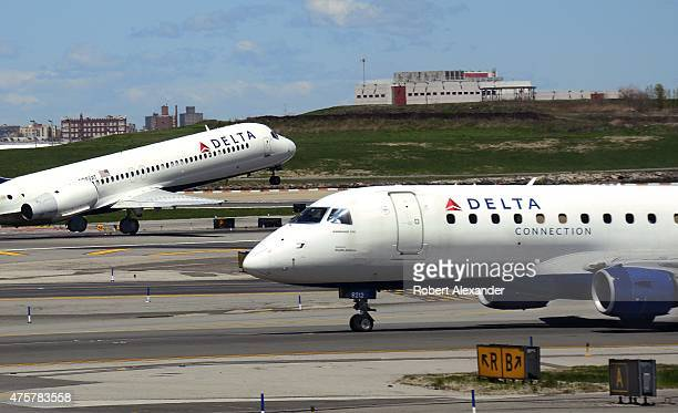 Delta Airlines and Delta Connection passenger aircraft taxi and take off at LaGuardia Airport in New York City New York