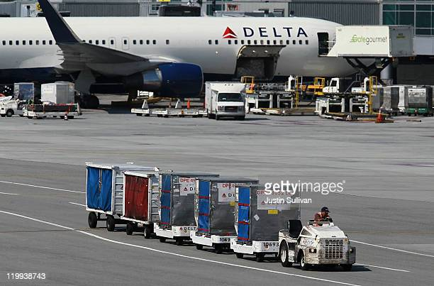 Delta Airlines baggage cart drives by a Delta Airlines plane at San Francisco International Airport on July 27 2011 in San Francisco California Delta...