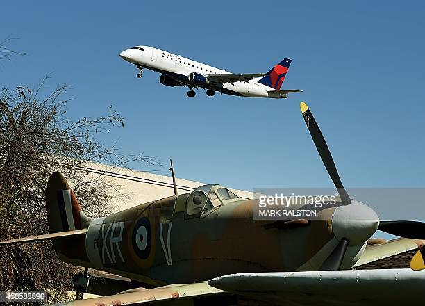 A Delta Airlines flight flies past a World War Two vintage Spitfire as it lands at the Los Angeles International Airport California on November 7...