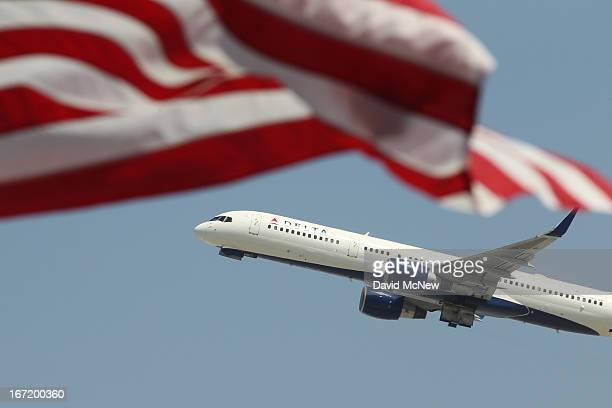 Delta Airlines jet passes an American flag during takeoff at Los Angles International Airport on April 22 2013 in Los Angeles California Delays have...
