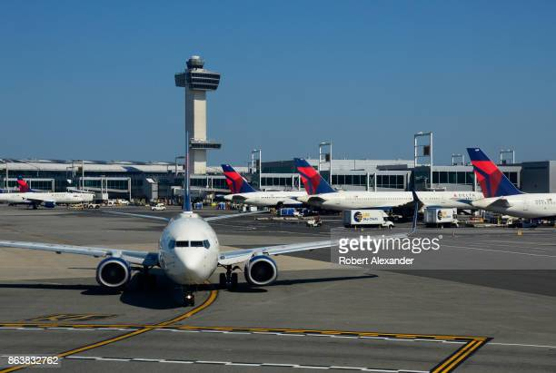 Delta Airlines passenger jet taxis at John F Kennedy International Airport in New York New York with the airport's 32 story 321foot tall control...