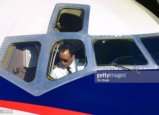 Delta Airlines pilot is seen through a cockpit window after arriving December 5 2000 at the Delta Airlines terminal of Chicago's O''Hare...