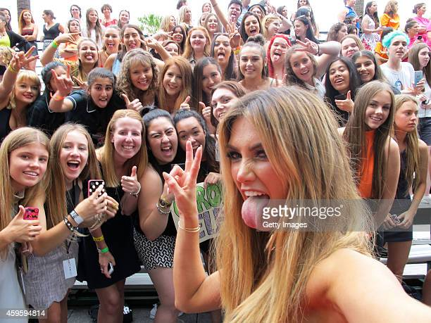 Delta Goodrem takes a selfie with fans upon arrival for the 28th Annual ARIA Awards 2014 at the Star on November 26 2014 in Sydney Australia