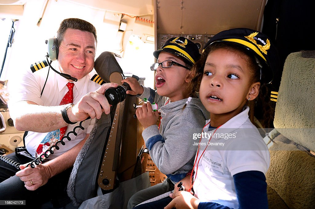 Delta pilot and children attend the 3rd Annual Garden of Dreams Foundation & Delta Air Lines' 'Holiday in the Hangar' event at John F. Kennedy International Airport on December 11, 2012 in New York City.