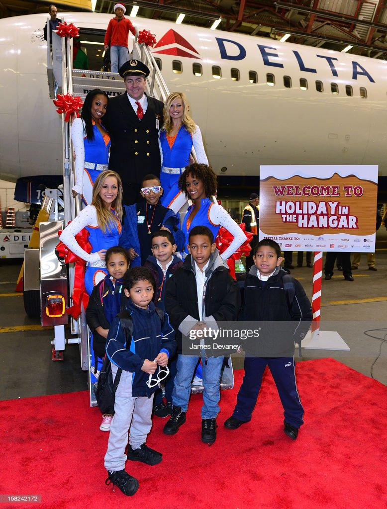A Delta pilot and the Knicks City Dancers pose with children at the 3rd Annual Garden of Dreams Foundation & Delta Air Lines' 'Holiday in the Hangar' event at John F. Kennedy International Airport on December 11, 2012 in New York City.