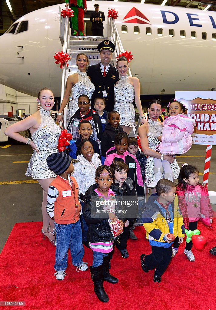 A Delta pilot and the Radio City Rockettes pose with children at the 3rd Annual Garden of Dreams Foundation & Delta Air Lines' 'Holiday in the Hangar' event at John F. Kennedy International Airport on December 11, 2012 in New York City.