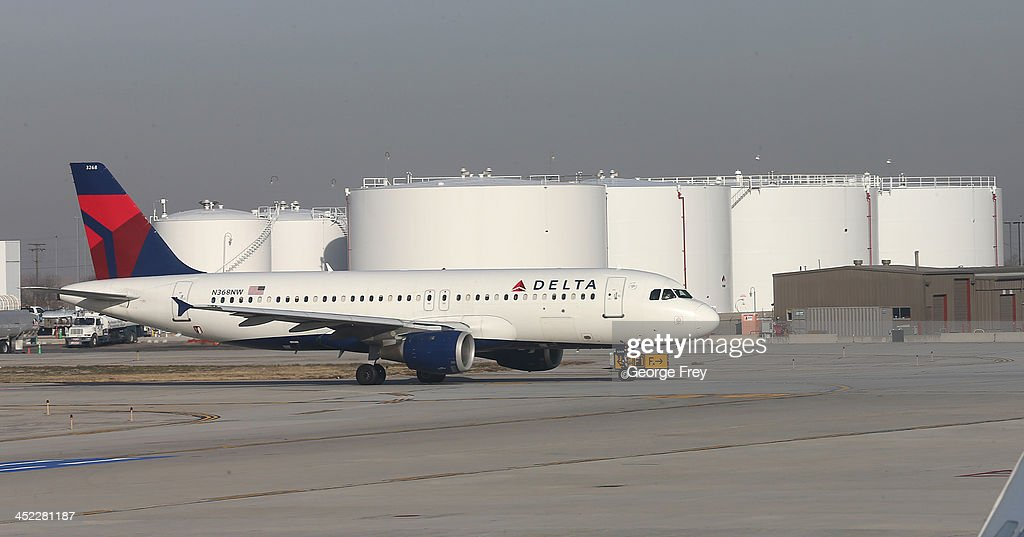A Delta plane taxies past large fuel tanks at the Salt Lake City international Airport on November 27, 2013 in Salt Lake City, Utah. A wintry storm system that is covering much of the nation is threatening to wreak havoc on holiday travel .