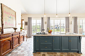Vast kitchen in a contemporary mansion, with a large kitchen island, antique cabinet and vast terrace windows