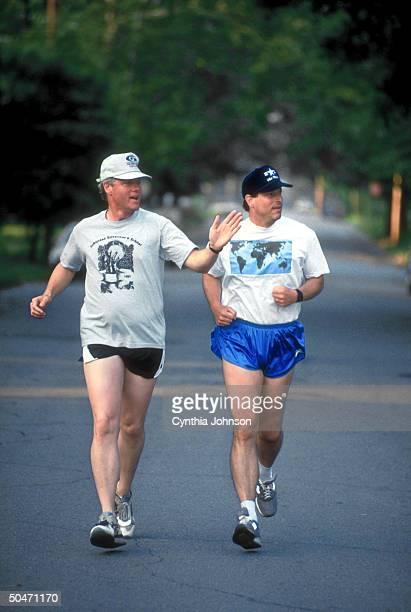 Dem presidential cand Bill Clinton newly named running mate Sen Al Gore jogging down street