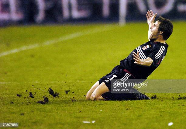 Dema Kovalenko of DC United slides on his knees to celebrate a goal by teammate Bryan Namoff against the MetroStars during the second half in the MLS...