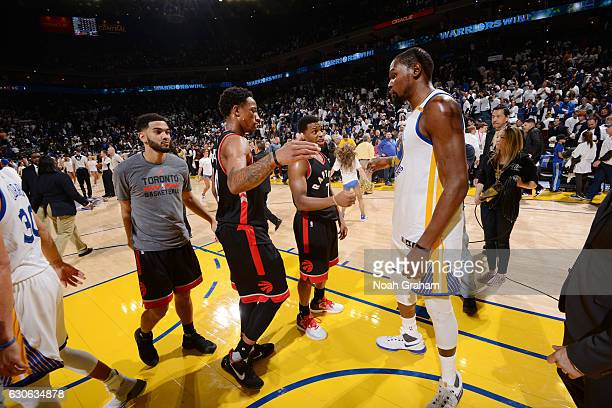 DeMar DeRozan and Kyle Lowry of the Toronto Raptors talk with Kevin Durant of the Golden State Warriors after a game on December 28 2016 at ORACLE...