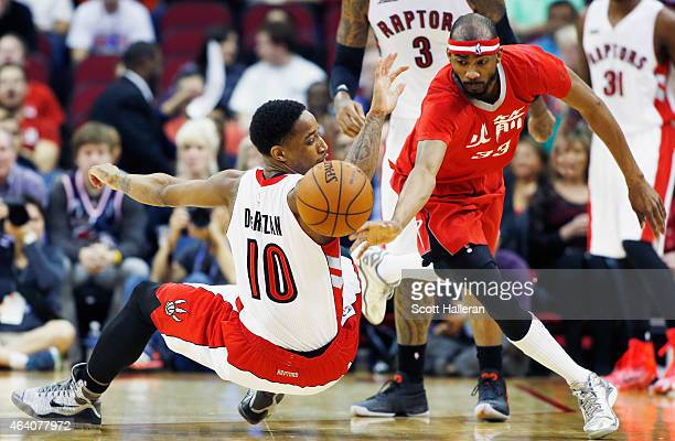 DeMar DeRozan of the Toronto Raptors and Corey Brewer of the Houston Rockets batlle for a loose basketball during their game at the Toyota Center on...