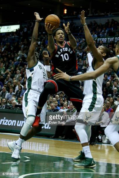 DeMar DeRozan of the Toronto Raptors attempts a shot between Tony Snell and Greg Monroe of the Milwaukee Bucks in the third quarter in Game Six of...