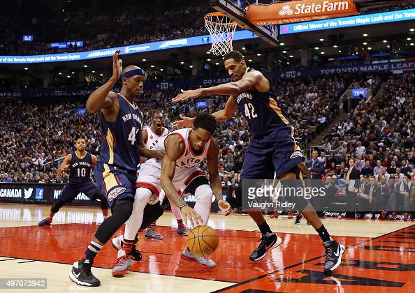 DeMar DeRozan of the Toronto Raptors dribbles the ball as Alexis Ajinca and Dante Cunningham of the New Orleans Pelicans defend during an NBA game at...