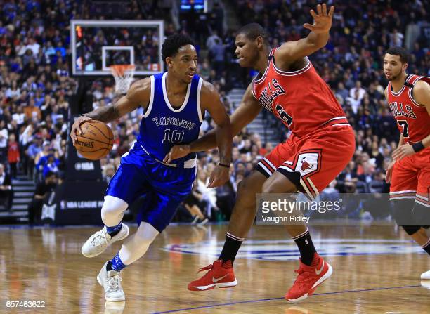 DeMar DeRozan of the Toronto Raptors dribbles the ball as Christiano Felicio of the Chicago Bulls defends during the first half of an NBA game at Air...