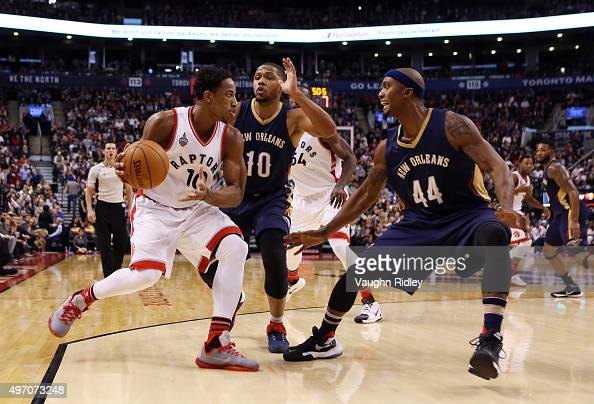 DeMar DeRozan of the Toronto Raptors dribbles the ball as Eric Gordon and Dante Cunningham of the New Orleans Pelicans defend during an NBA game at...