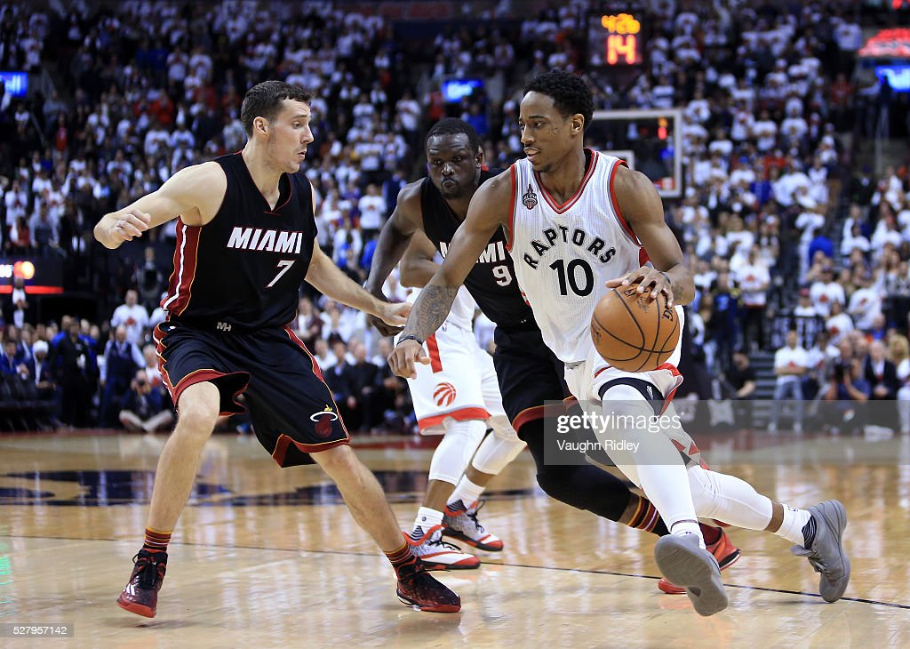 DeMar DeRozan of the Toronto Raptors dribbles the ball as Goran Dragic and Luol Deng of the Miami Heat defend in the second half of Game One of the...