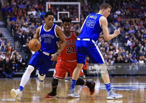 DeMar DeRozan of the Toronto Raptors dribbles the ball as Jimmy Butler of the Chicago Bulls defends during the first half of an NBA game at Air...