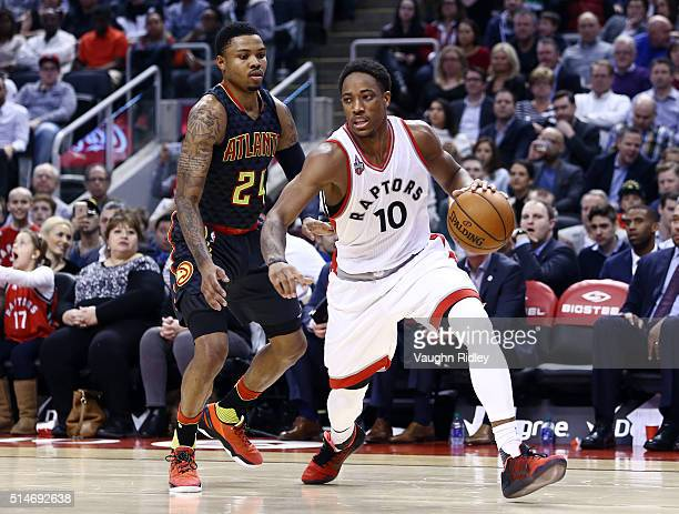 DeMar DeRozan of the Toronto Raptors dribbles the ball as Kent Bazemore of the Atlanta Hawks defends during the first half of an NBA game at the Air...