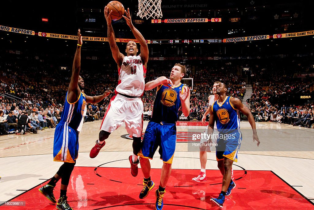 DeMar DeRozan #10 of the Toronto Raptors drives to the basket against <a gi-track='captionPersonalityLinkClicked' href=/galleries/search?phrase=Draymond+Green&family=editorial&specificpeople=5628054 ng-click='$event.stopPropagation()'>Draymond Green</a> #23 and David Lee #10 of the Golden State Warriors on January 28, 2013 at the Air Canada Centre in Toronto, Ontario, Canada.