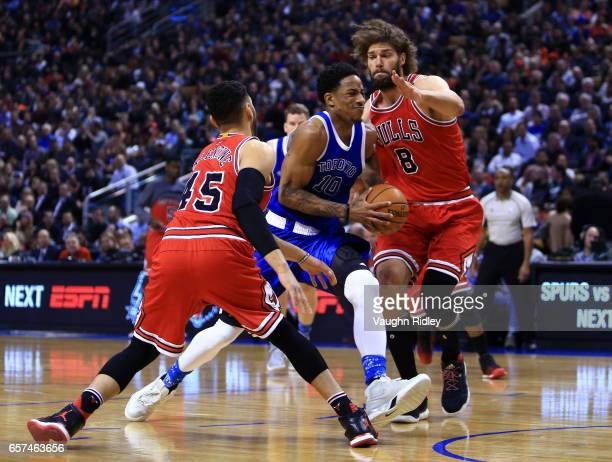 DeMar DeRozan of the Toronto Raptors drives to the basket as Denzel Valentine and Robin Lopez of the Chicago Bulls defend during the first half of an...