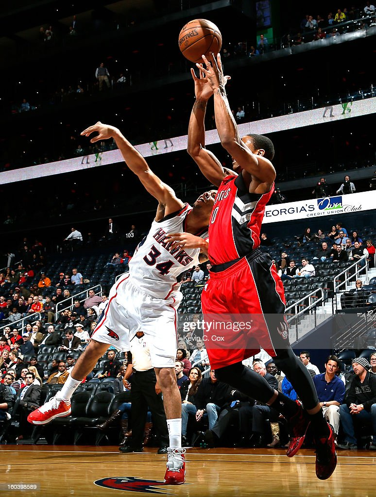 DeMar DeRozan #10 of the Toronto Raptors grabs a pass against Devin Harris #34 of the Atlanta Hawks at Philips Arena on January 30, 2013 in Atlanta, Georgia.