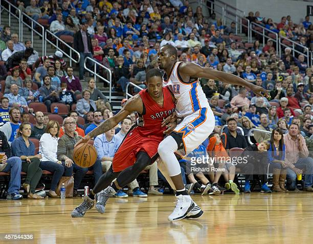 DeMar DeRozan of the Toronto Raptors handles the ball against Serge Ibaka of the Oklahoma City Thunder on October 17 2014 at the Intrust Bank Arena...