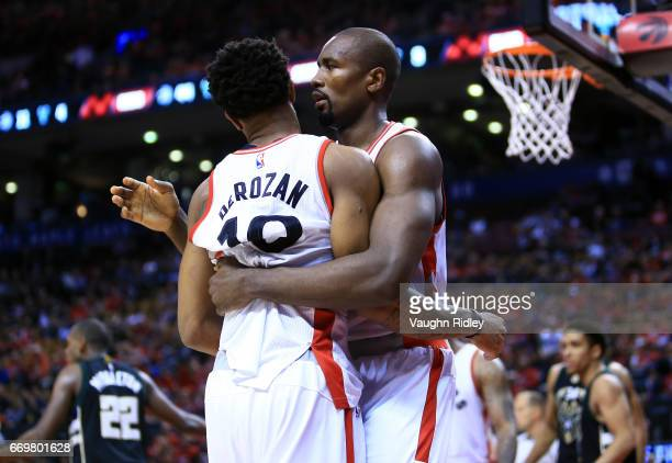 DeMar DeRozan of the Toronto Raptors is held back by teammate Serge Ibaka after being fouled by Giannis Antetokounmpo of the Milwaukee Bucks in the...