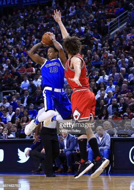 DeMar DeRozan of the Toronto Raptors passes the ball as Robin Lopez of the Chicago Bulls defends during the first half of an NBA game at Air Canada...