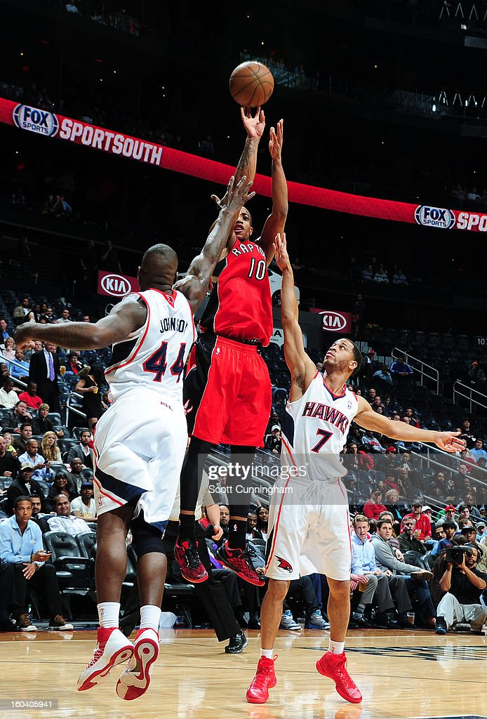 DeMar DeRozan #10 of the Toronto Raptors shoots against Ivan Johnson #44 and Jannero Pargo #7 of the Atlanta Hawks on January 30, 2013 at Philips Arena in Atlanta, Georgia.