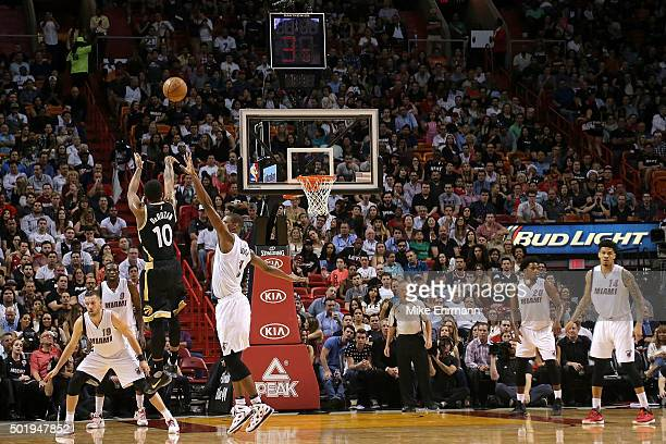 DeMar DeRozan of the Toronto Raptors shoots over Chris Bosh of the Miami Heat during a game at American Airlines Arena on December 18 2015 in Miami...