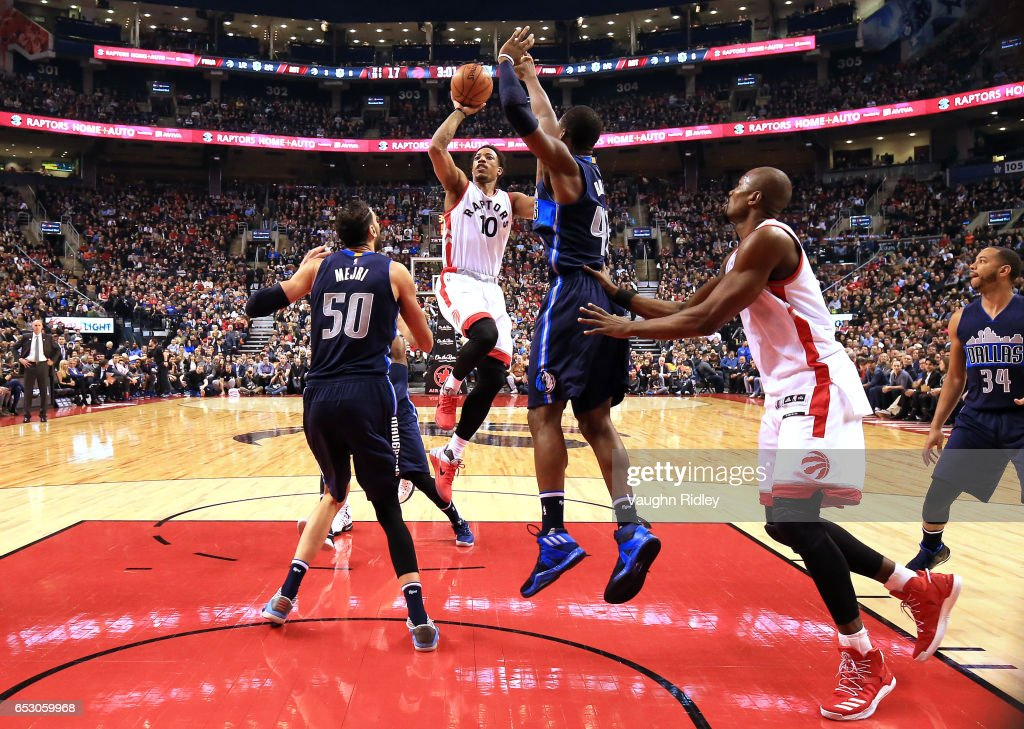 DeMar DeRozan #10 of the Toronto Raptors shoots the ball as Salah Mejri #50 and Harrison Barnes #40 of the Dallas Mavericks defend during the first half of an NBA game at Air Canada Centre on March 13, 2017 in Toronto, Canada.