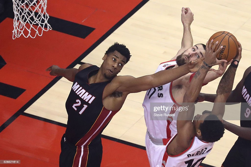DeMar DeRozan pulls down a rebound as Jonas Valanciunas and Hassan Whiteside reach as the Toronto Raptors play the Miami Heat in game two of their Eastern Conference Semifinal at the Air Canada Centre in Toronto. May 5, 2016.