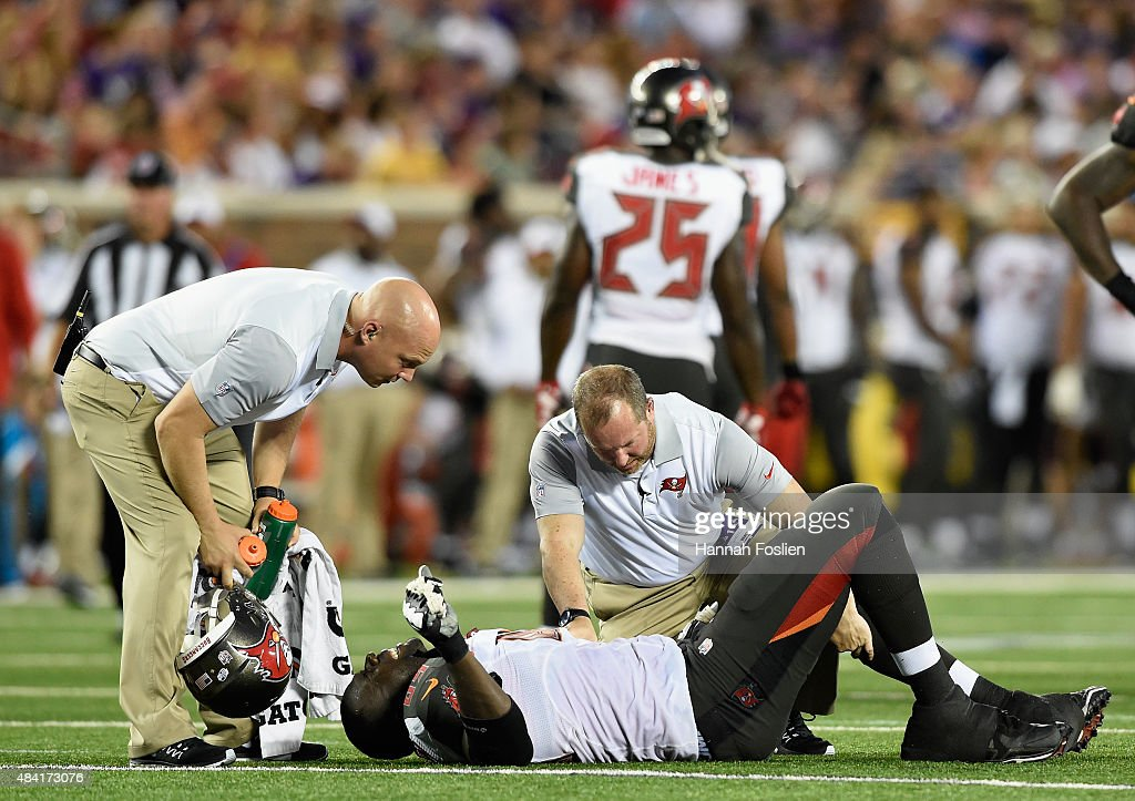 Demar Dotson #69 of the Tampa Bay Buccaneers is looked at by trainers after an injury during the second quarter of the preseason game against the Minnesota Vikings on August 15, 2015 at TCF Bank Stadium in Minneapolis, Minnesota.
