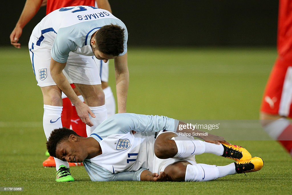 Demarai Gray of England U21 lies on the pitch after being fouled while he is helped by his teammate Matthew Grimes during the European Under 21 Qualifier match between Switzerland U21 and England U21 at Stockhorn Arena on March 26, 2016 in Thun, Switzerland.