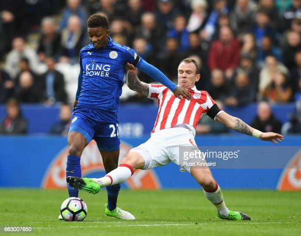 Demarai Gray of Leicester City is tackled by Glenn Whelan of Stoke City during the Premier League match between Leicester City and Stoke City at The...