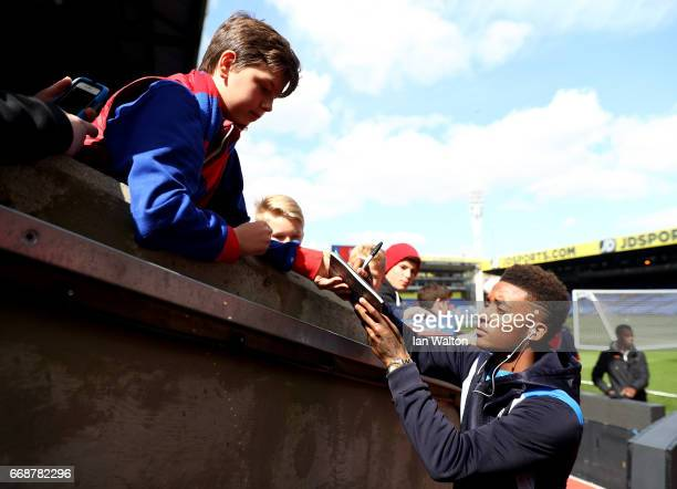 Demarai Gray of Leicester City signs fans autographs as he arrives at the stadium prior to the Premier League match between Crystal Palace and...