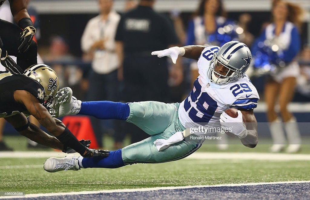 DeMarco Murray of the Dallas Cowboys scores a touchdown against Corey White of the New Orleans Saints at ATT Stadium on September 28 2014 in...
