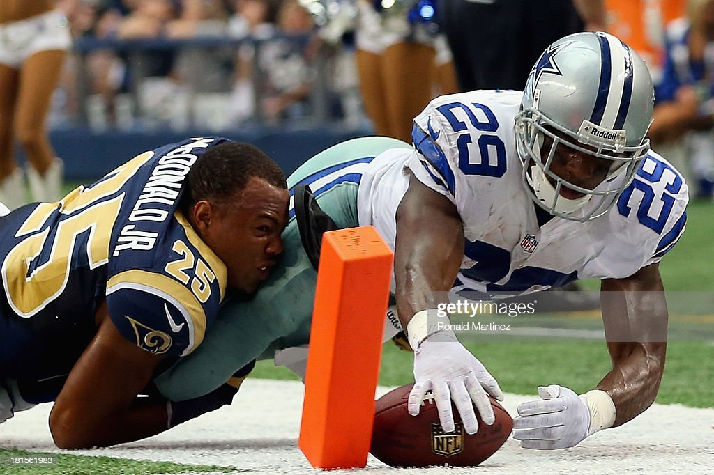 DeMarco Murray of the Dallas Cowboys scores a touchdown while tackled by TJ McDonald of the St Louis Rams at ATT Stadium on September 22 2013 in...