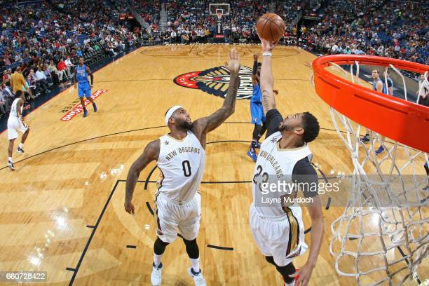DeMarcus Cousins and Anthony Davis of the New Orleans Pelicans go up for a rebound against the Dallas Mavericks on March 29 2017 at the Smoothie King...