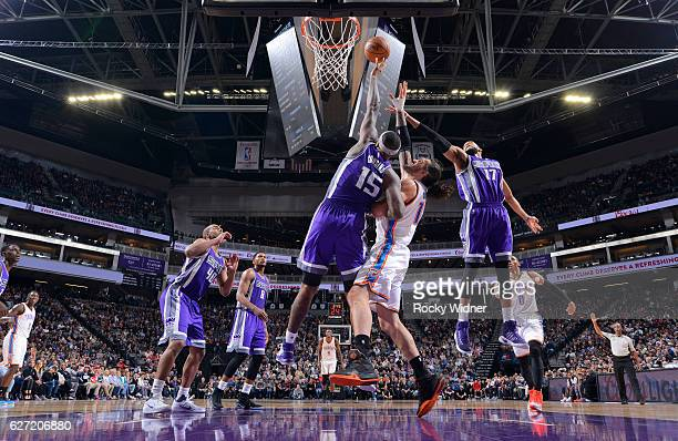DeMarcus Cousins and Garrett Temple of the Sacramento Kings rebound against Steven Adams of the Oklahoma City Thunder on November 23 2016 at Golden 1...