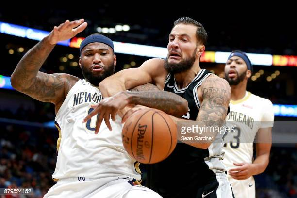 DeMarcus Cousins of the New Orleans Pelicans scrambles for a loose ball with Joffrey Lauvergne of the San Antonio Spurs during the first half of a...
