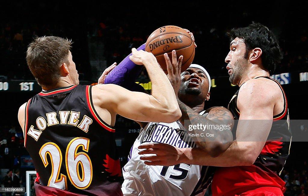 DeMarcus Cousins #15 of the Sacramento Kings draws a foul from Zaza Pachulia #27 of the Atlanta Hawks at Philips Arena on February 22, 2013 in Atlanta, Georgia.