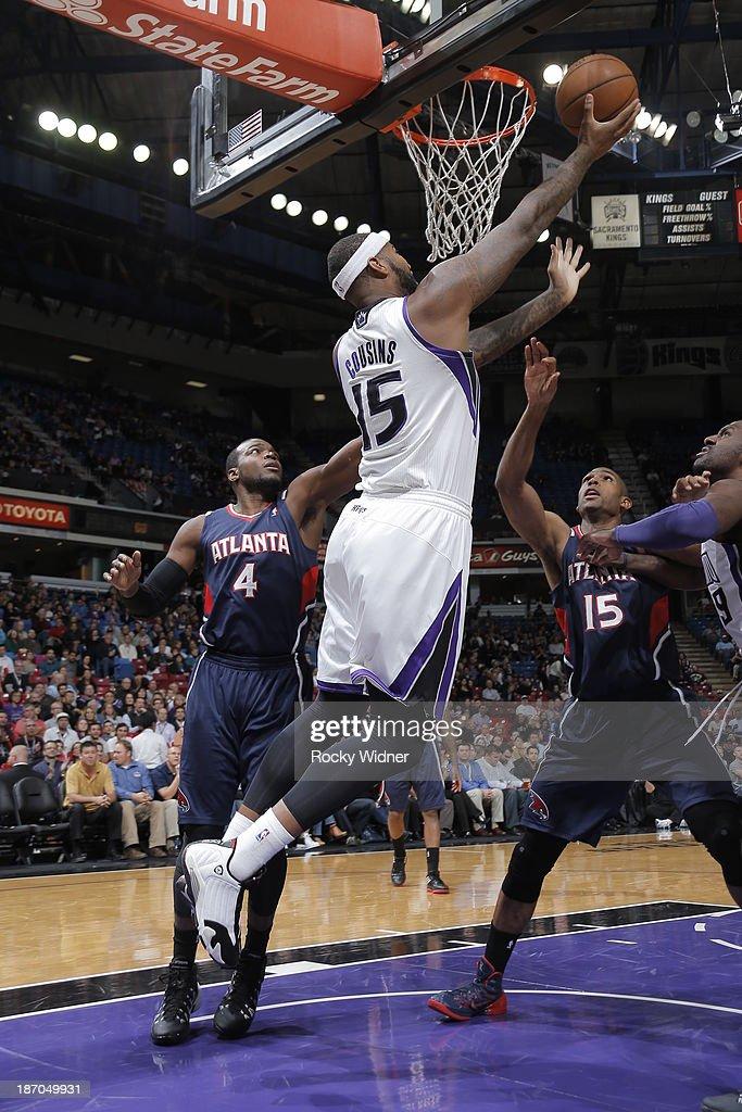 DeMarcus Cousins #15 of the Sacramento Kings shoots a reverse layup against Paul Millsap #4 of the Atlanta Hawks at Sleep Train Arena on November 5, 2013 in Sacramento, California.