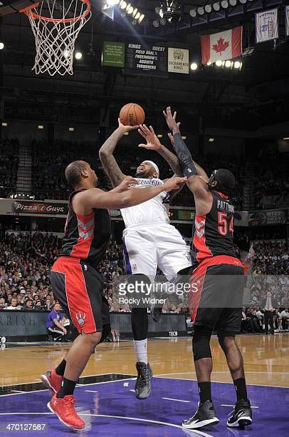 DeMarcus Cousins of the Sacramento Kings shoots against Chuck Hayes and Patrick Patterson of the Toronto Raptors on February 5 2014 at Sleep Train...
